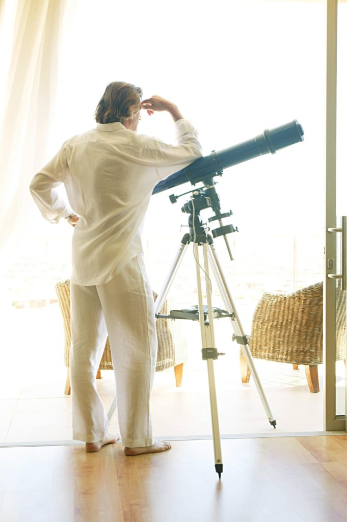 Man leaning on telescope