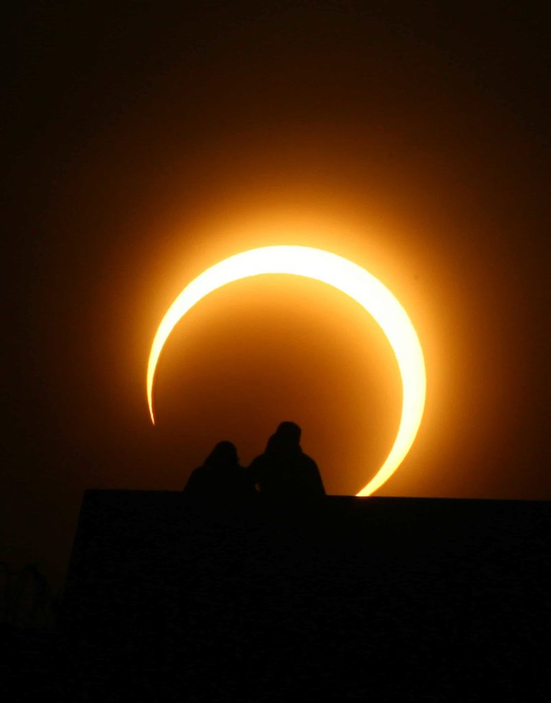 A Chinese couple watches the solar eclipse over Zhengzhou, central China's Henan province on January 15, 2010. A solar eclipse that reduced the sun to a blazing ring surrounding a sombre disk plunged millions of people in Africa and Asia into an eerie semi-darkness, as the spectacle, visible in a roughly 300-kilometre (185-mile) band running 12,900 kilometres (8,062 miles) across the globe, set a record for the longest annular eclipse that will remain unbeaten for more than a thousand years. CHINA OUT AFP PHOTO (Photo credit should read STR/AFP/Getty Images)