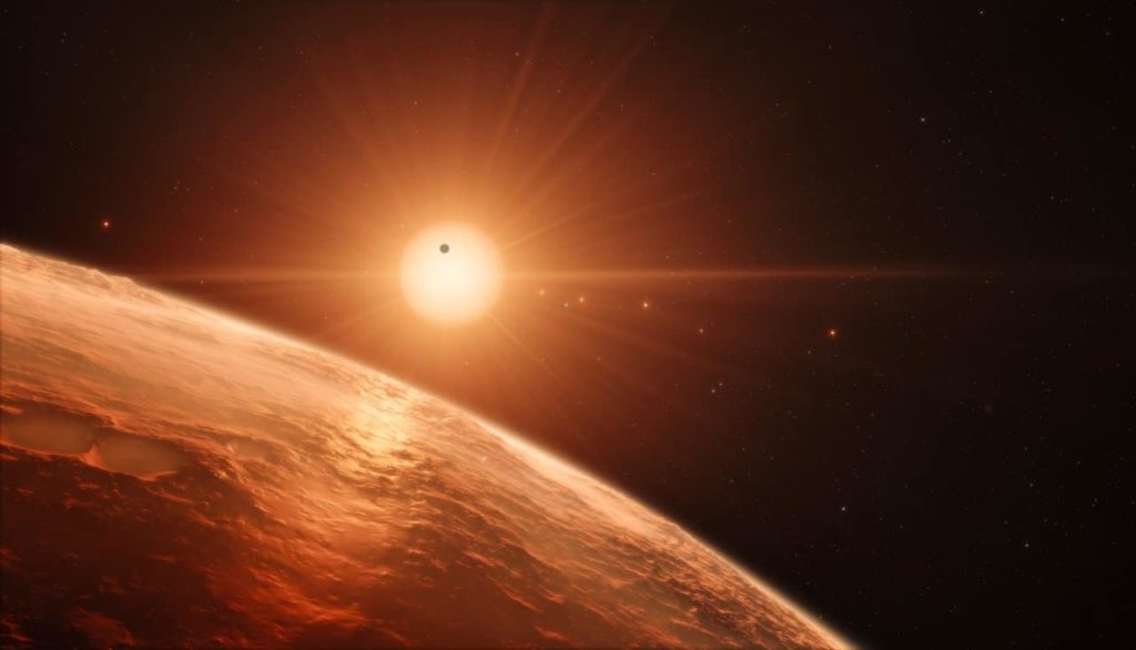 This artist's impression shows the view from the surface of one of the planets in the TRAPPIST-1 system. At least seven planets orbit this ultra cool dwarf star 40 light-years from Earth and they are all roughly the same size as the Earth. They are at the right distances from their star for liquid water to exist on the surfaces of several of them. Thisartist's impression is based on the known physical parameters for the planets and stars seen, and uses a vast database of objects in the Universe.