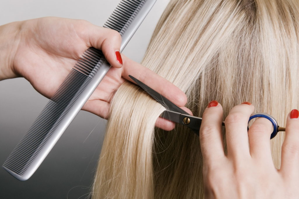 hairdresser cutting blonde hair. closeup over grey background