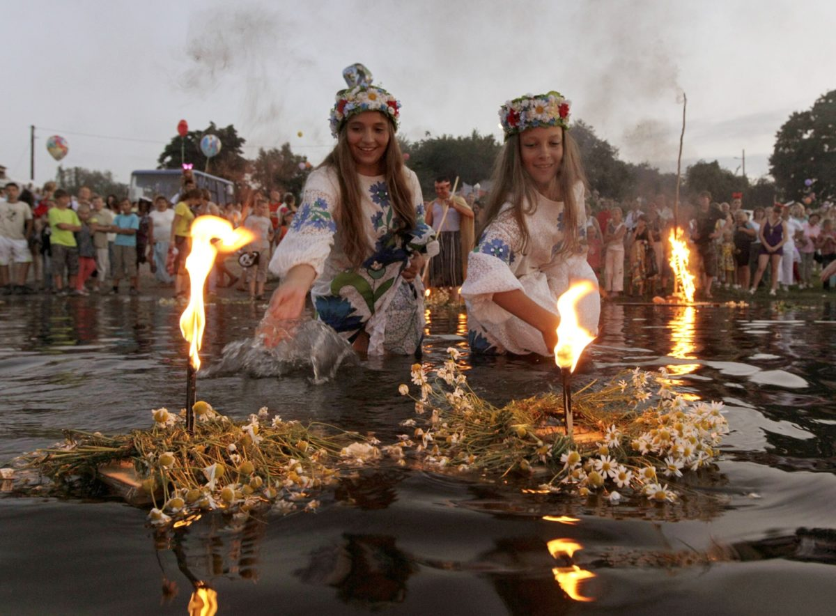 Image: Belarusian girls float wreaths with candles as they take part in the Ivan Kupala festival in the town of Turov
